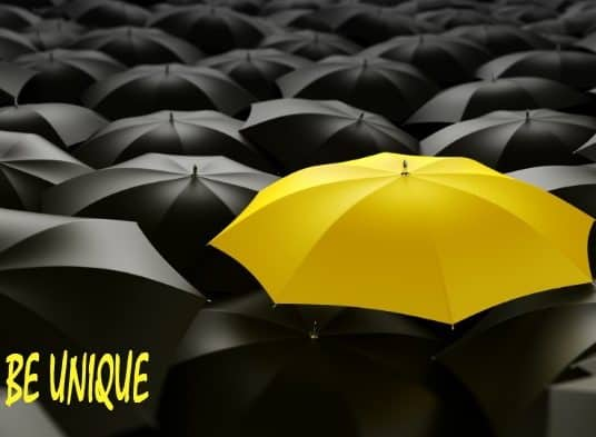 yellow umbrella in a see of black umbrellas
