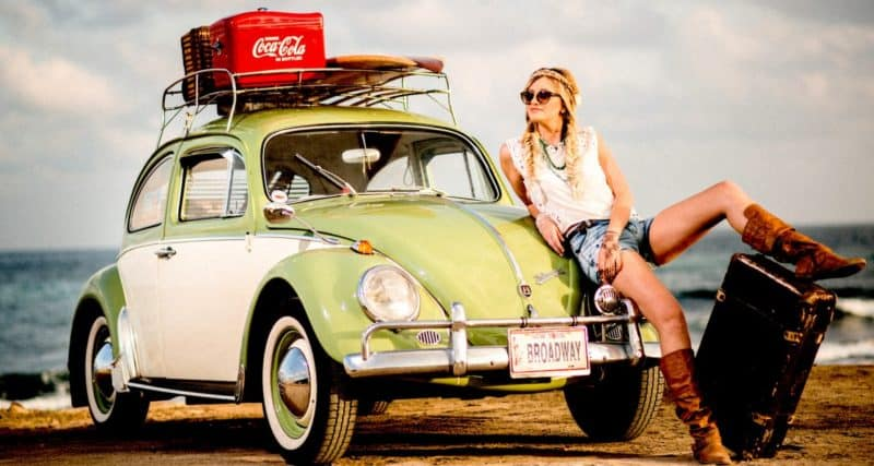 Woman leaning against voltswagon bug thinking